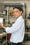 Store keeper. At work holding red wine stock photography