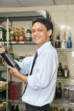 Store keeper. At work holding red wine stock photo