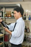 Store keeper or auditor. Store keeper checking the quality of wine royalty free stock photos