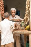 Store keeper specializing in garlic talks to customer in window. Trinidad, Cuba, Nov 27, 2017 - Store keeper specializing in garlic talks to customer in window stock image