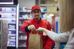 At Store. Male Worker At Store Giving To Female Costumer Goods Which She Bought Royalty Free Stock Photos
