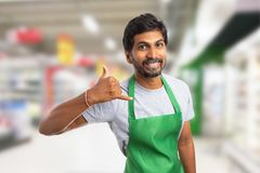 Store manager making call me gesture. Indian male store manager or hypermarket employee having friendly smile making call me gesture with fingers at ear stock photos