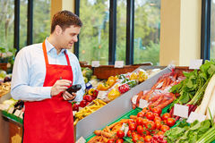 Store manager ordering vegetables with data terminal. Store manager in supermarket ordering fresh vegetables with mobile data registration terminal stock images