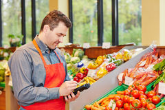 Store manager in supermarket using. A mobile data registration terminal Stock Photo