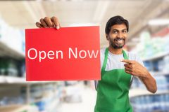 Store owner presenting open now sign. Indian male store owner or employee with friendly and trustworthy smile presenting open now sign on red paper stock photography