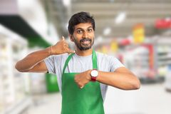 Store owner showing call if you are late concept. Indian male store owner or supermarket employee showing call if you are late concept with phone gesture and stock images