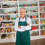 Store Owner Smiling In Supermarket Stock Photo