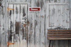Store Sign And Bench. Store Sign On Grey Wooden Wall stock photos
