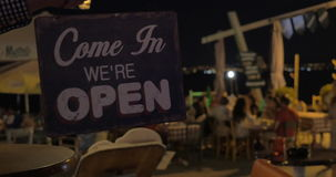 Store sign closed is turned to open at night on beach cafe background Thessaloniki, Greece stock video footage