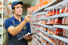 Store worker counting stock. Good looking hardware store worker counting stock Royalty Free Stock Images