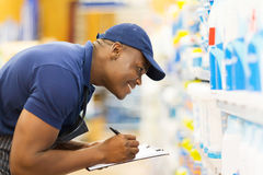 Store worker taking stock. Cheerful african hardware store worker taking stock Stock Photography