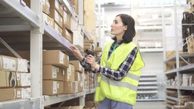 Store worker in the warehouse using a barcode scanner conducts accounting stock video footage