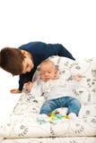 Storebror som att bry sig hans sömniga syster Royaltyfria Bilder