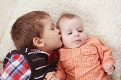 Storebror som kysser behandla som ett barn Arkivbild