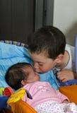 Storebrorkyssar behandla som ett barn systern Arkivfoton