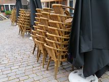 Stored chairs and parasols at a terrace. A stack of chairs and black sunscreens on a empty terrace in the city Royalty Free Stock Photography