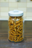 Stored fusilli pasta. Dry fusilli pasta in a covered glass jar Stock Images