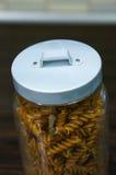 Stored fusilli pasta. Dry fusilli pasta in a covered glass jar Stock Photo