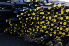 Stored many black steel pipe with heat insulation on construction site in a plastic tube wrapper lying  with yellow lids pipes. For supplying gas heat pressure Royalty Free Stock Photography