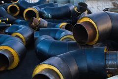 Stored many black steel withdrawal pipe with heat insulation on construction site  close up in a plastic tube wrapper lying  pipes Royalty Free Stock Image