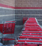 Stored Red Shopping Carts and Wall. Red shopping carts lined up outside facing colorful striped wall Royalty Free Stock Photo