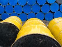 Stored stacks of colorful metal oil barrels. Yellow and blue industrial metal petroleum drums stacked for storage Royalty Free Stock Photos