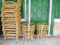 Stored terrace chairs. A stack of rotan chairs and tables in front of a house with green shutters and a green door Royalty Free Stock Photography
