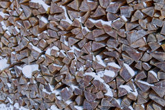 Stored wood. Snow-covered stacked firewood outside in winter Royalty Free Stock Photo