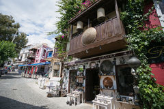 Storefront of antique shop in Kalkan. KALKAN, TURKEY - MAY 22 Storefront of antique shop decorated with shelves with antique metal trays jugs lanterns and other Royalty Free Stock Photos