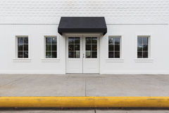 Storefront building with black awning. White empty building with black awning royalty free stock photography