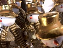 On the storefront shop colorful toys snowmen in golden hats stock images
