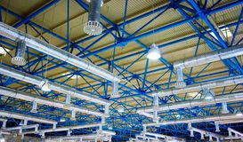 Storehouse ceiling. Mosern contemporary architecture: inner part of supermarket roof - ceiling - with lamps, ventilation tubing and support structure Stock Photos