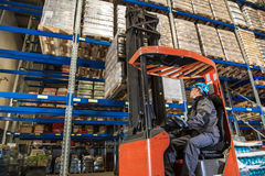 Storehouse employee during driving on forklift in warehouse royalty free stock photography