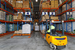 Storehouse logistic. Forklift driver handling goods in distribution storehouse Royalty Free Stock Image