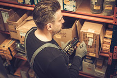 Storekeeper with handheld barcode scanner working in a warehouse. Storekeeper with mobile computer working in a warehouse royalty free stock photo