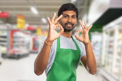 Storekeeper holding fingers as okay gesture. Friendly indian male storekeeper or hypermarket employee holding fingers as double okay gesture stock images