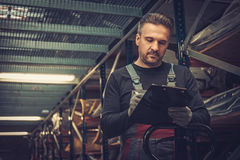 Storekeeper with manual pick list on a warehouse royalty free stock images