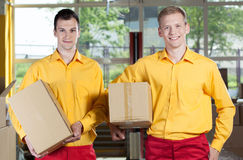 Storekeepers holding boxes in warehouse Royalty Free Stock Photos