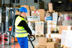 Storeman with mover at warehouse of forwarding. Warehouseman in protective vest pulls a mover with packages and boxes at warehouse of freight forwarding company Stock Photo