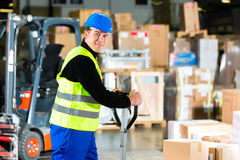 Storeman with mover at warehouse of forwarding. Warehouseman in protective vest pulls a mover with packages and boxes at warehouse of freight forwarding company Stock Images