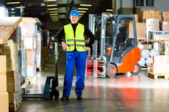 Storeman with mover at warehouse of forwarding. Warehouseman in protective vest holds a mover, standing beside packages and boxes at warehouse of freight Royalty Free Stock Photo