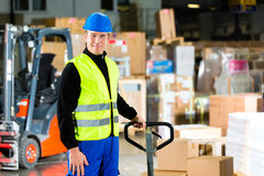 Storeman with mover at warehouse of forwarding. Warehouseman in protective vest pulls a mover with packages and boxes at warehouse of freight forwarding company Stock Image