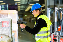 Storeman with scanner at warehouse of forwarding. Warehouseman in protective vest using a scanner, standing beside packages and boxes at warehouse of freight Stock Photos