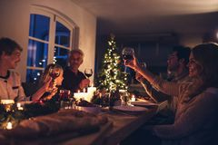 Storfamilj som rostar vin på julmatställen arkivfoton