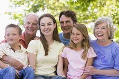 storfamilj som sitter utomhus att le Royaltyfri Bild