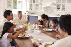 Storfamiljgrupp som hemma äter mål tillsammans arkivfoton