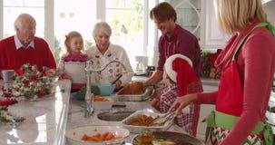Storfamiljgruppen förbereder jullunch i kök - fadertagandekalkon från ugnen och tråcklar den med skeden