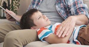 Storia del libro elettronico della lettura del padre al figlio che si rilassa sul suo rivestimento stock footage