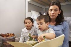 Storia della lettura della madre ai bambini nella loro camera da letto Fotografie Stock