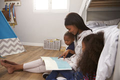 Storia della lettura della madre ai bambini nella loro camera da letto Immagine Stock